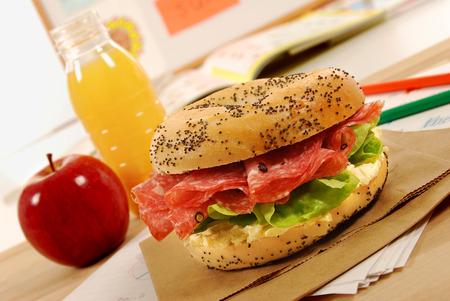 apple paper bag: School lunch of salami bagel sandwich Stock Photo