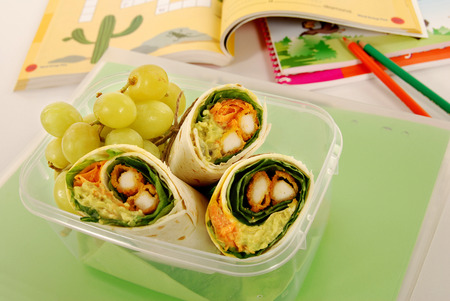 lunch: School lunch of fried chicken & avocado wrap sandwich Stock Photo