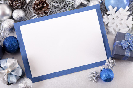 christmas tree decoration: Blank Christmas card or invitation with blue envelope surrounded by decorations. Space for copy.