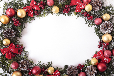 retain: Christmas wreath with traditional decorations and berries in snow. Space for copy.  Note to buyers: I have not blown out the central copy space to pure white in order to retain the background paper texture.