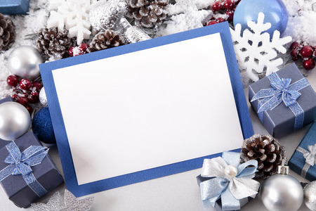 christmas bow: Blank Christmas card or invitation with blue envelope surrounded by decorations. Space for copy.