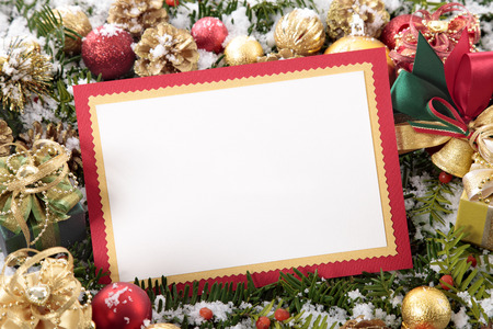 photo frame: Blank Christmas card or invitation with red envelope surrounded by decorations. Space for copy.