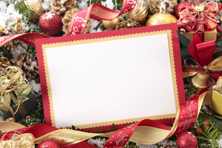 baubles: Blank Christmas card or invitation with red envelope surrounded by decorations. Space for copy.