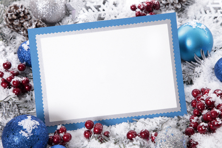 Blank Christmas card or invitation with blue envelope surrounded by decorations. Space for copy.