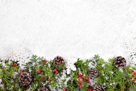 Christmas border with decorations on the snow. Space for copy.