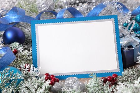 cajas navide�as: Tarjeta de Navidad en blanco con el sobre azul rodeado de decoraciones. Espacio para la copia.