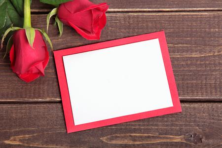 papier a lettre: Valentine background de roses rouges et une carte sur le bois. Espace pour la copie.