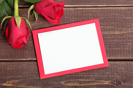 love letter: Valentine background of  red roses and card on wood. Space for copy. Stock Photo