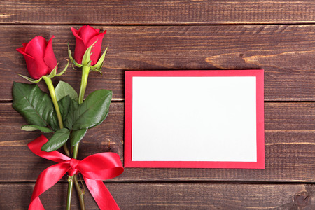 love letter: Valentine blank card and two roses on wood Stock Photo