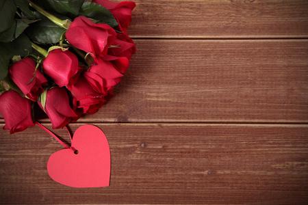 rosas rojas: Fondo de San Valentín de la etiqueta de regalo y rosas rojas en la madera. Espacio para la copia.