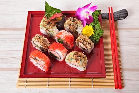 california roll: California roll sushi with chopsticks displayed on mat Stock Photo