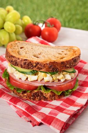 火腿和鸡蛋野餐三明治在夏天室外桌上