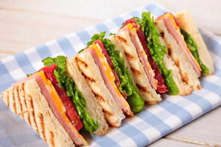Sommer-Picknick-Club-Sandwich Schinken und Käse in einer Reihe Standard-Bild