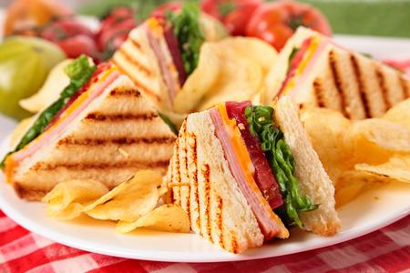 Zomerpicknick club sandwich ham en kaas, chips Stockfoto