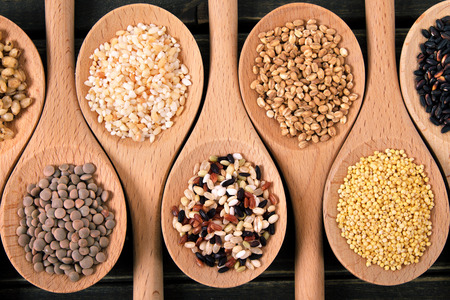 Variety of rice and grains in spoons on wooden table