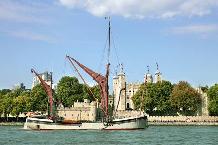 Traditional Thames Barge sailing on the River Thames with Tower of London in the background