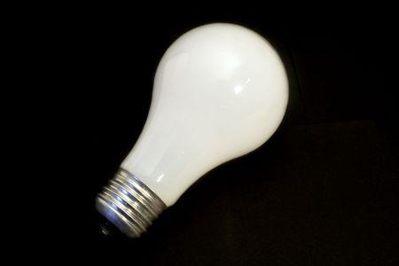 Lightbulb on black background Фото со стока