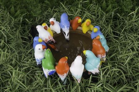 Group of colorful bird statue are meeting in garden Stock Photo