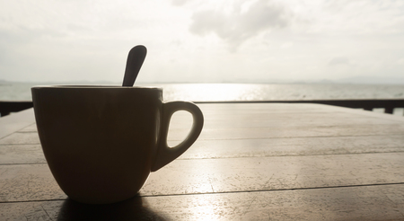 Closeup coffee cup at beach cafe in silhouette style