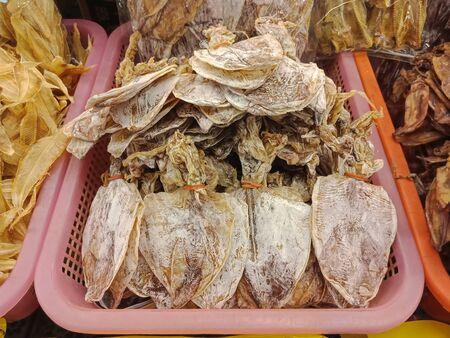 Group of Dry squid in plastic basket for sale, Thai food Foto de archivo