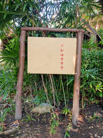Empty Banner signpost  with arrow in green garden resort