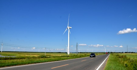 Wind turbines beside a highway Editorial