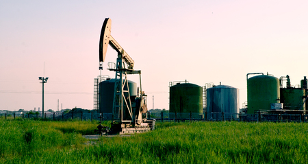 Oil derricks with industrial tanks Stock Photo