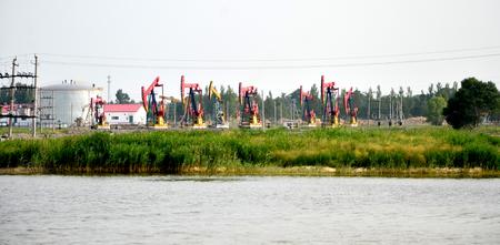 Oil derricks beside a lake