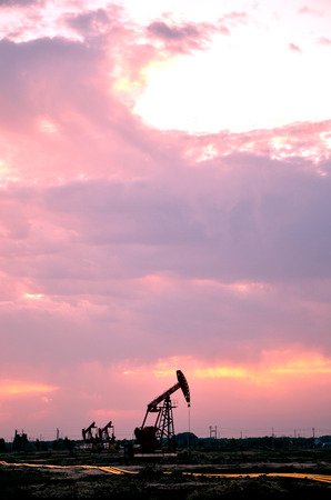 Oil pump jacks in a field under sunset sky Editorial