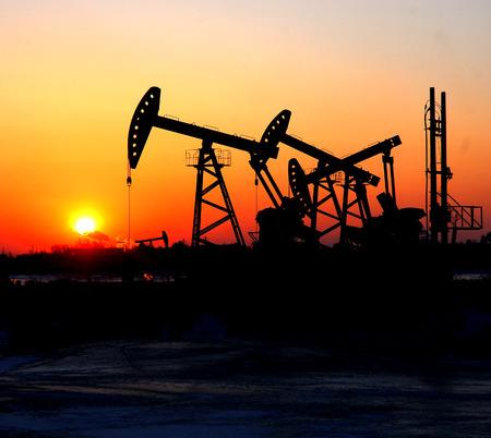 Oil pump jacks over sunset background