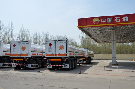 Oil tanker trucks with natural gas beside a gas station