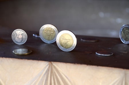 thai believe: Placing the vertical coins believe at Wat thai
