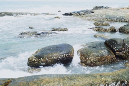 onto: Waves crashing onto rocks in the sea