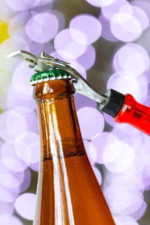 Opening dark beer bottle with metal opener photo