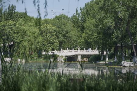 White marble stone bridge on the lake in Chinese garden