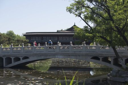 Finely carved white marble eight-hole stone bridge on a pond in a Chinese garden