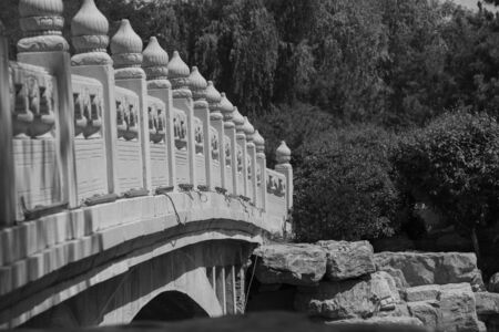The railings of the finely carved white marble eight-hole stone bridge on the pond in the Chinese garden