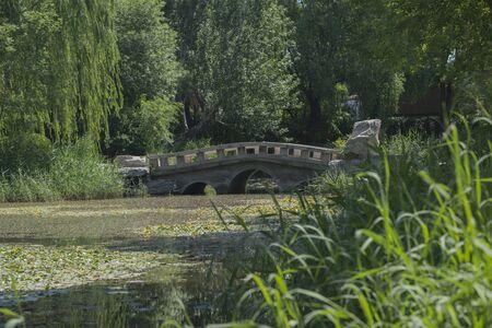 Small stone bridge over pond in Chinese garden 版權商用圖片