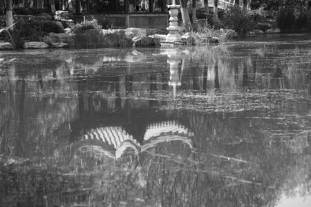 Reflection of the gazebo in the Chinese garden in the pond