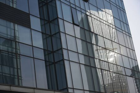 Scenery reflected from glass curtain wall of high-rise modern building in downtown