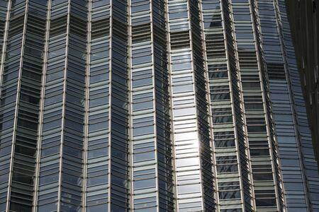 Close-up of glass facade of high-rise modern building in downtown