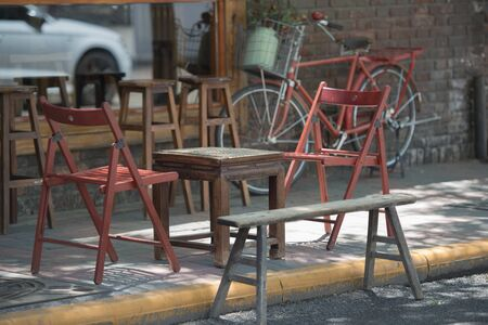 Folding chairs, chess tables and benches in the shade of the street