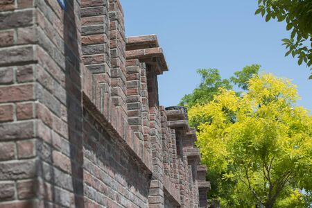 Red brick courtyard wall among green trees on city street 版權商用圖片