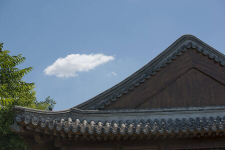 White clouds floating on the ridge of a traditional house building in a Chinese garden
