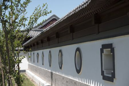 Gray tile fence with through windows in Chinese garden