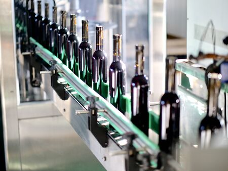 the filled red wine bottles is being produced on the assembly line
