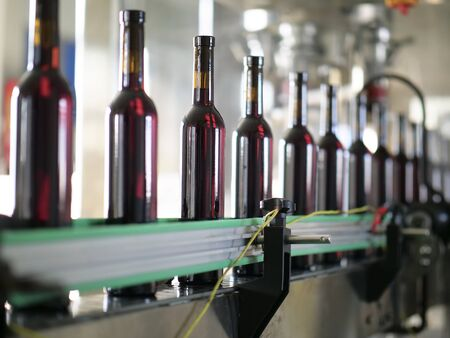the filled red wine bottles is being produced on the assembly lin