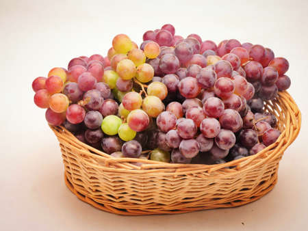 Red grapes in the fruit basket, White background
