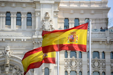 palacio de comunicaciones: Flag of Spain in the wind in front of Palace of Communication (Spanish: Palacio de Comunicaciones) in Madrid, Spain Stock Photo