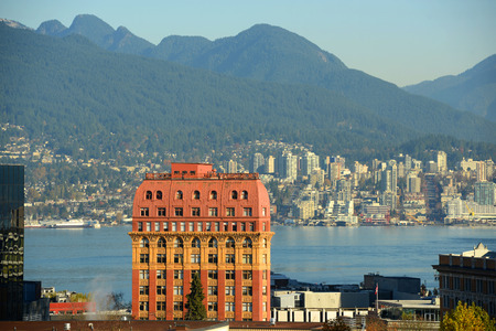 dominion: Historic Second Empire style Dominion Building and North Vancouver city skyline across Vancouver Harbour, Vancouver, British Columbia, Canada.